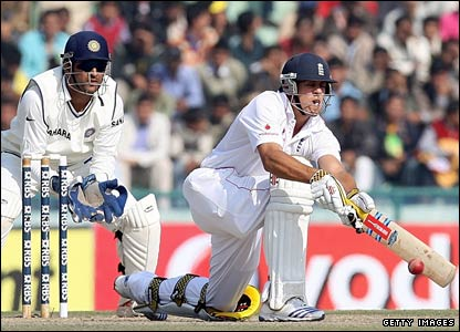 Alastair Cook sweeps, watched by India captain and keeper Mahendra Dhoni