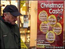 Man beside sign offering loans