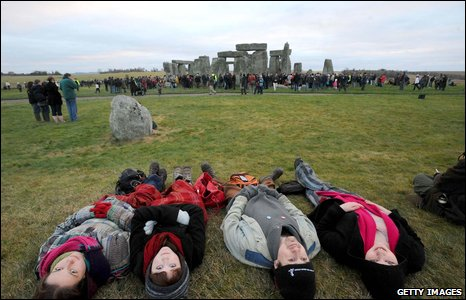Group lie on the floor at Stonehenge