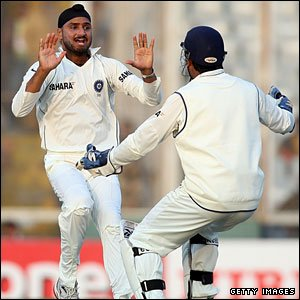 Harbhajan Singh celebrates the wicket of Kevin Pietersen with Mahendra Dhoni