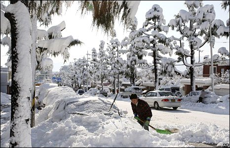 A South Korean driver cleans snow off his car after heavy snow hit the north-eastern region overnight in Sokcho, South Korea