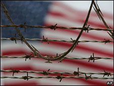 Barbed wire at Quantanamo Bay, with a US flag in the background