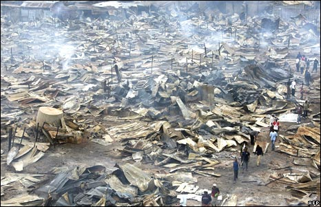 Residents of Kibera slum walk past the smouldering remains of what used to be a second hand clothes market in Nairobi, Kenya, 31 December 2007