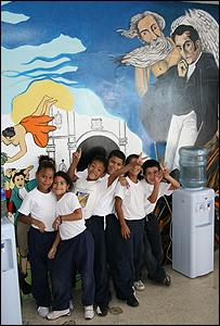 Ni�os frente a un mural en la entrada de la escuela bolivariana en el barrio 23 de Enero en Caracas