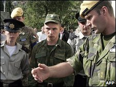 Georgian police hand a Russian army conscript (c) to OSCE representatives in Mtskheta, some 20 kms outside Tbilisi