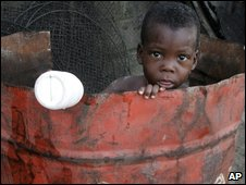 Nigerian child plays inside an oil drum