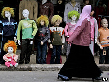 Palestinian woman walks past mannequins in Ramallah (21 December 2008)