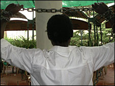A person holds up chained arm. (Photo: Farug website www.faruganda.org)