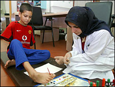 Ali Ismail Abbas being guided by a therapist at a hospital in Kuwait City, 8 June 2003