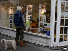 A man looks at house adverts in an estate agent's window