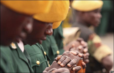 Soldiers of the Presidential Guard bow their heads as President Robert Mugabe delivers a speech