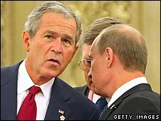 George Bush in whispered conversation with Vladimir Putin