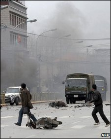 Tibetans throw stones at army vehicles as a car burns on a street in the Tibetan capital Lhasa, March 2008