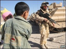An Iraqi boy carrying a baby passes a British soldier in Basra, 16 December