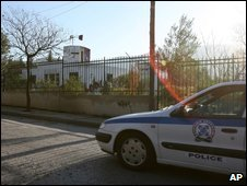 A police car passes the site of the attack on a police bus in Athens