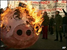 Demonstrators burn a paper pig's head outside the Greek parliament in Athens