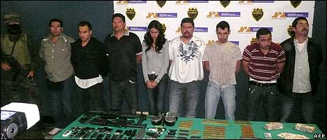 Laura Zuniga (centre) stands handcuffed along with seven fellow detainees under armed guard
