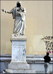 A worker paints over graffitti on one of the buildings of the University of Athens