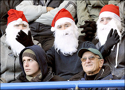 Chelsea v West Brom: Three Father Christmas fans enjoy the festive football at Stamford Bridge