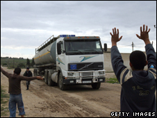 Palestinian children watch the arrival of a fuel truck into the Gaza Strip