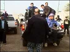 Police in Ramadi remove bodies from the scene of the jailbreak (still from Reuters TV)