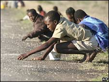 Zimbabwe's children and their parents pick up single corn kernels spilled on the road side by trucks ferrying maize corn. Photo: 14 December 2008