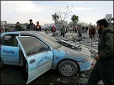 Damaged police car and civilians in Gaza