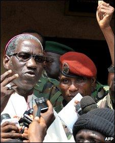 Capt Moussa Dadis Camara (in red beret) arrives at meeting alongside Bishop Vincent Colibaly