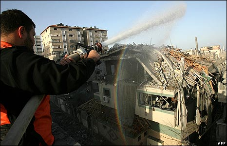 A Palestinian fireman douses a building hit in the air strikes in Gaza City
