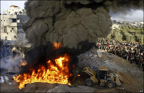 A bulldozer tries to push sand on a fire after an Israeli missile strike in Rafah