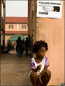 A girl sits at the entrance of a polling station in Accra