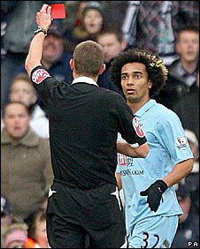 Referee Steve Tanner shows Benoit Assou-Ekotto a red card
