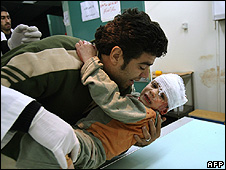A wounded Palestinian boy is carried by his father in hospital in Gaza City, 28 Dec 08