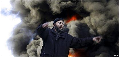 Hombre gesticula frente al lugar en el que cayó una bomba