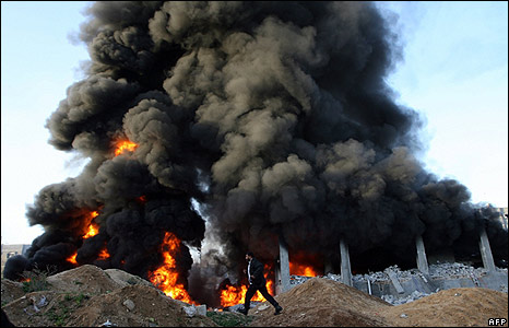 Man rushes past burning building in Rafah, 28 Dec 08