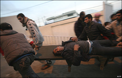 Wounded Palestinian man being carried on stretcher in Rafah