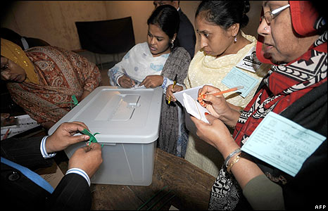 A polling officer locks the ballot box in front of polling agents in Dhaka