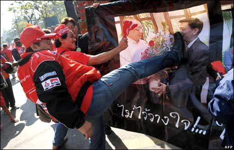 Pro-Thaksin protesters kick a poster of PM Abhisit