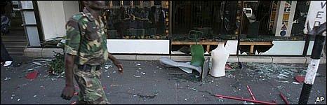 Zimbabwean soldier walks past looted shop
