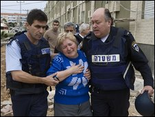 Police help an Israeli woman in shock following a rocket attack from Gaza on south Israeli town of Sderot (29/12/2008)