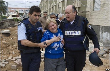 Israeli policemen help an Israeli woman in shock in Sderot