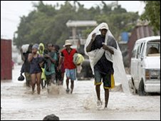 Haitians wade through a street flooded by Hurricane Ike in Gonaives (07/09/2008)