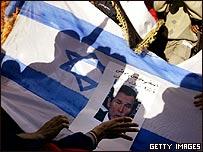 Bandera de Israel y foto del presidente de EE.UU. en manifestación.