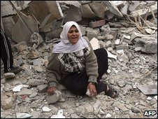 A Palestinian woman sits amid the rubble of a bombed house in Rafah, southern Gaza Strip, 29 December 2008