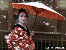 A traditional Japanese maiko walks in the snow in Gion - archive image
