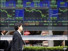 Man walks past Tokyo stockmarket indicator board