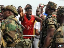 Soldiers try to calm down opposition supporters outside the electoral commission headquarters in Accra on 30 December 2008