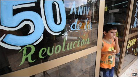 A boy eats ice-cream next to a shop window with the words '50th Anniversary of the Revolution', in Havana 28 December 2008