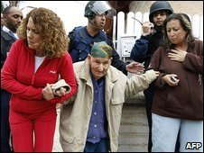 Israeli residents help an elderly woman after a rocket attack on Sderot, 30 December 2008