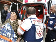 Israeli paramedics evacuate a woman in shock after a rocket attack on Sderot, 30 December 2008
